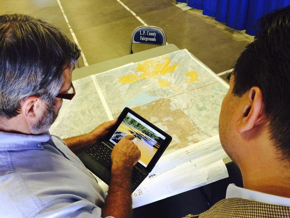 | Courtesy the Utah attorney general's office Utah Attorney General Sean Reyes examines a photo of Animas River days after the Gold King mine spill, when heavy metals turned the waters bright yellow.