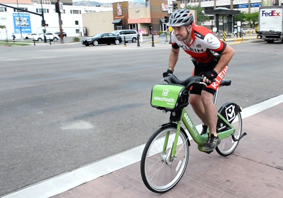 (Rick Egan | The Salt Lake Tribune) Salt Lake Tribune reporter Ben Wood crosses 200 East on his Green Bike at the start of a race against colleagues from Library Square to the Tribune building at the Gateway on Thursday, Aug. 2, 2018.