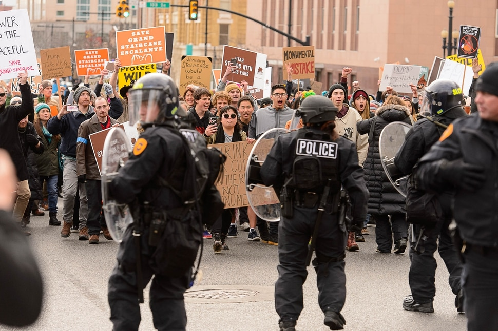 (Trent Nelson | The Salt Lake Tribune) Police back up as protesters approach downtown after a rally against a visit by President Donald Trump, Monday December 4, 2017.