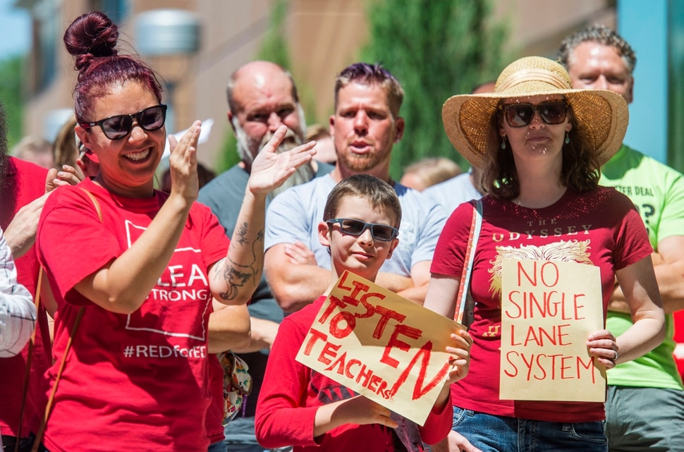 (Rick Egan | The Salt Lake Tribune) Jenn Gilpatrick, Shannon Herbert, and 9-year-old Finn Herbert join teachers from the Salt Lake School District as they hold a rally at Innovations High School, Tuesday, June 18, 2019.