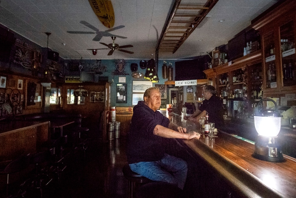 (Noah Berger | AP) Joseph Pokorski drinks a beer at The Town Square as downtown Sonoma, Calif., remains without power on Wednesday, Oct. 9, 2019. Pacific Gas and Electric has cut power to more than half a million customers in Northern California hoping to prevent wildfires during dry, windy weather throughout the region.