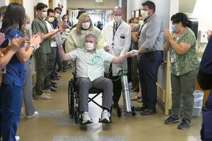 """(Intermountain Healthcare) Thomas Kearl, in wheelchair, leaves Intermountain Medical Center Aug. 24, 2021, after spending 223 days in the hospital while sick with COVID-19. Kearl requested that Kenny Loggins' song """"Celebrate Me Home"""" be played as he said farewell to the medical team that cared for him."""