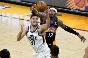 Utah Jazz forward Georges Niang (31) pulls down a rebound over Phoenix Suns forward Torrey Craig (12) during the first half of an NBA basketball game, Wednesday, April 7, 2021, in Phoenix. (AP Photo/Matt York)