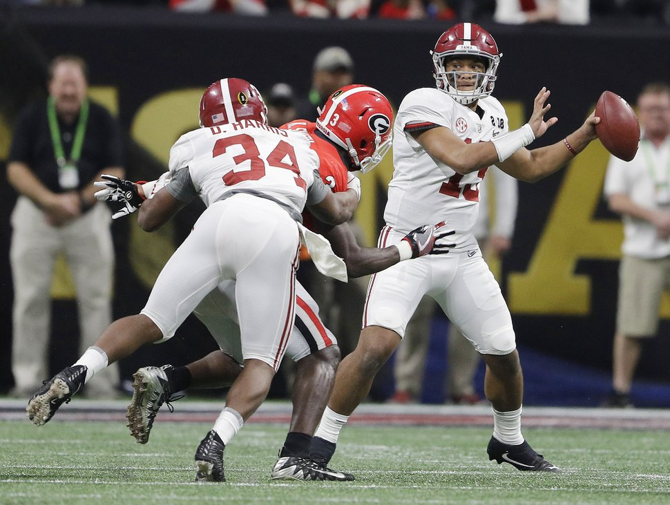 File- This Jan. 8, 2018, file photo shows Alabama quarterback Tua Tagovailoa dropping back to pass during the second half of the NCAA college football playoff championship game against Georgia in Atlanta. Tagovailoa is fighting for the starting job at Alabama after leading the Crimson Tide to a second-half comeback in last year's national championship game. The strong-armed lefty threw for 166 yards and three touchdowns in the win over Clemson. (AP Photo/David J. Phillip, File)