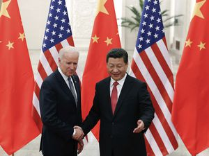 (Lintao Zhang | AP file photo)  In this Dec. 4, 2013, photo, Chinese President Xi Jinping, right, shakes hands with then U.S. Vice President Joe Biden as they pose for photos at the Great Hall of the People in Beijing.
