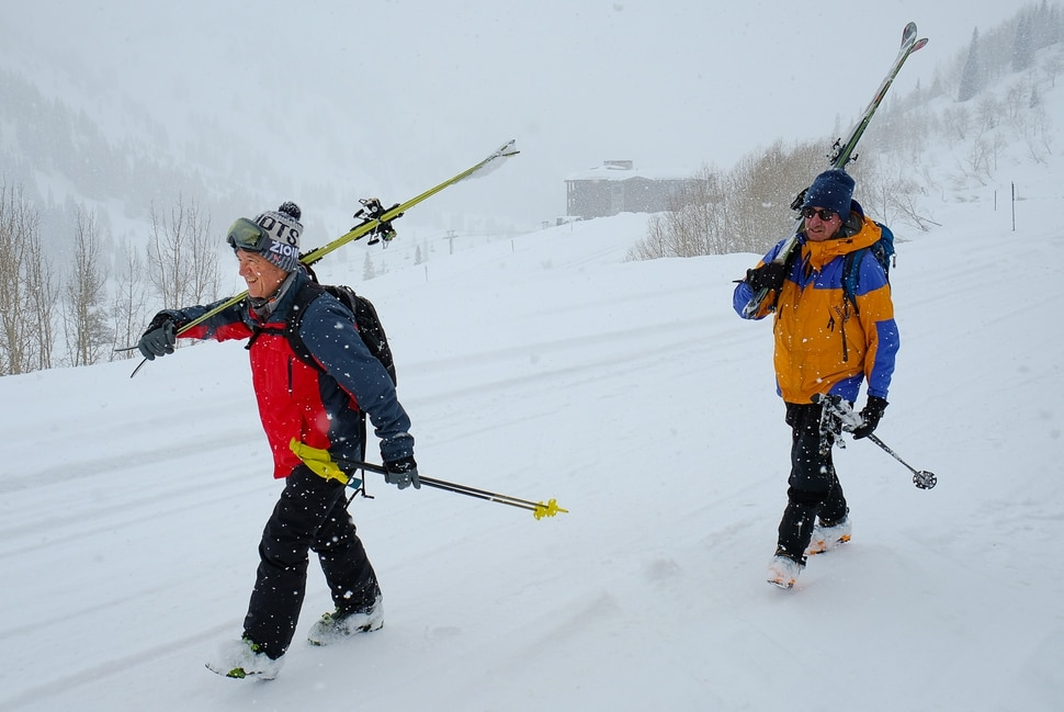 (Francisco Kjolseth | The Salt Lake Tribune) Rob Kirschner, left, and Ira Goodsmith maintain social distancing in the wake of the coronavirus outbreak as they meet up in separate cars near the Alta Ski Resort on their way up the Summer Road on Wednesday, March 25, 2020. With all the resorts closed, skiers are taking advantage of new snowfall by turning to uphill skiing -- basically backcountry skiing within a resort's boundaries. Alta so far has allowed this on some of its terrain, but closed their uphill traffic on Wednesday for avalanche control except for the Summer Road and Grizzly Gulch.