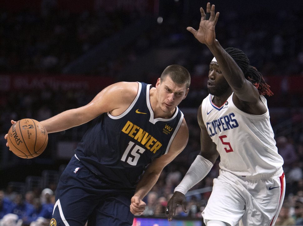 Denver Nuggets center Nikola Jokic, left, drives toward the basket as Los Angeles Clippers forward Montrezl Harrell defends during the first half of an NBA preseason basketball game in Los Angeles on Thursday, Oct. 10, 2019. (AP Photo/Kyusung Gong)