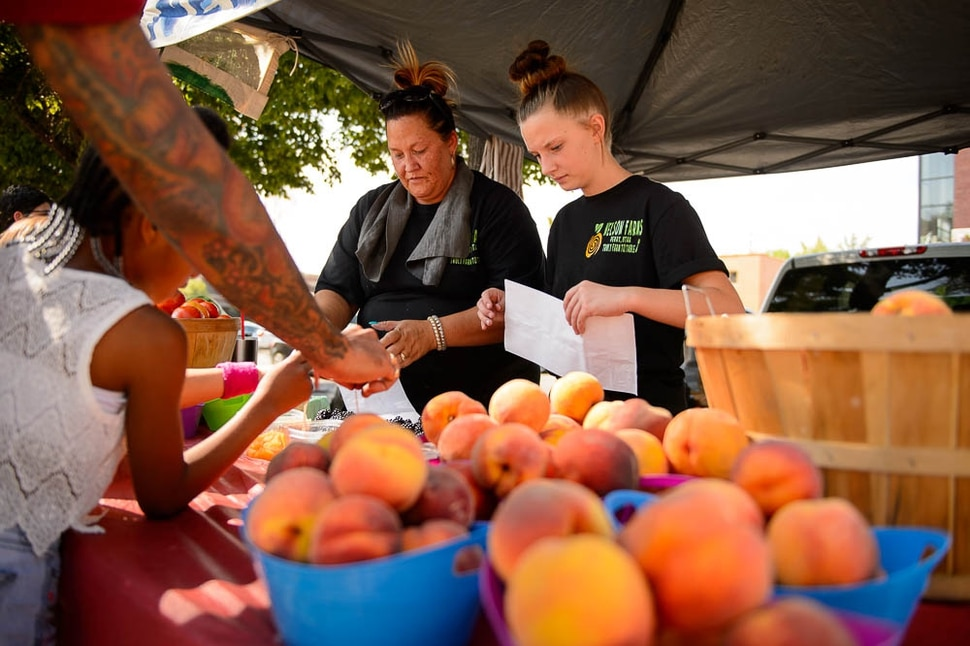 (Trent Nelson | The Salt Lake Tribune) April and Brittney Nelson of Nelson Farms at the Tuesday Farmer's Market in Salt Lake City's Pioneer Park, Tuesday Aug. 14, 2018. The laid-back market continues now through September and features about 20 vendors.