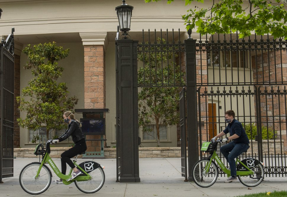(Rick Egan | The Salt Lake Tribune) Tourists wear masks as they ride bikes past the tabernacle in Salt Lake CIty, Wednesday, May 20, 2020.