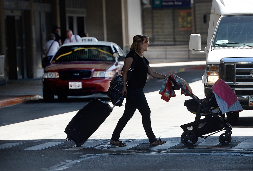 Scott Sommerdorf | The Salt Lake Tribune A traveler walks past a taxi dropping off a passenger at the Salt Lake International Airport, Wednesday, July 20, 2016. There have been some complaints from airport visitors about largely unregulated taxi fares. Cabs no longer need to have meters, can largely charge any fare they want (with some exceptions in SLC itself), and need not tell passengers in advance how much they will charge.