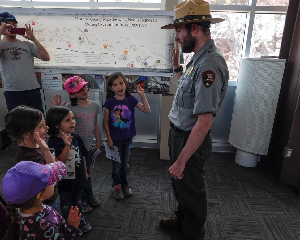 Erin Alberty | The Salt Lake Tribune Children repeat the Junior Ranger oath with Ranger John Isom on Saturday, May 27, 2017, in the Quarry Exhibit Hall at Dinosaur National Monument.