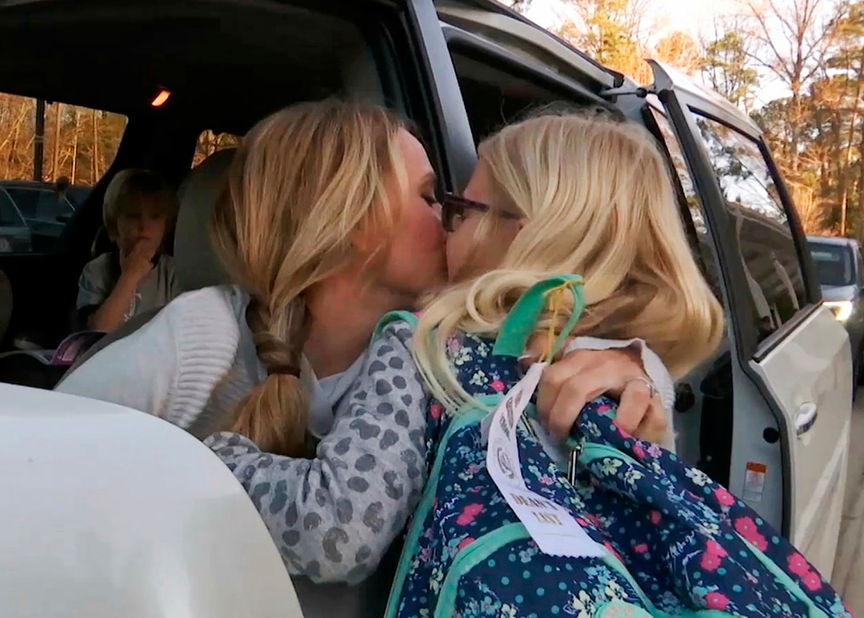 In this Wednesday, March 27, 2019, frame from video, Kacey Ruegsegger Johnson kisses her daughter, Logan, as she drops her off at her school in Cary, N.C. Dropping her kids off at school used to be the hardest part of Ruegsegger Johnson's day. She would cry most mornings as they left the car, and relied on texted photos from their teachers to make it through the day. (AP Photo/Allen G. Breed)