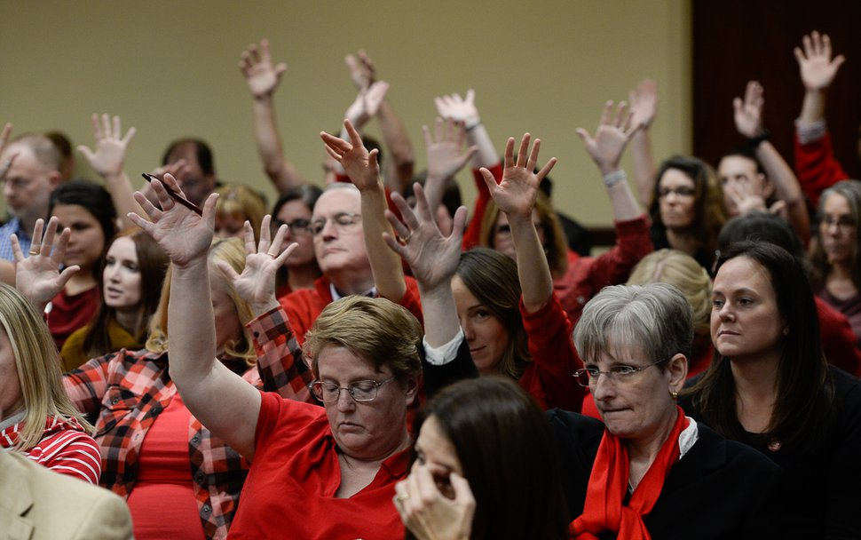 (Francisco Kjolseth | The Salt Lake Tribune) Teachers in red with buttons that read #red for ed, wave their hands in support of comments made for education at the tax reform task force has what may be its final meeting at the Utah Capitol on Monday, Nov. 25, 2019, with teachers turning out in large numbers to oppose any weakening of guarantee for public ed funding.