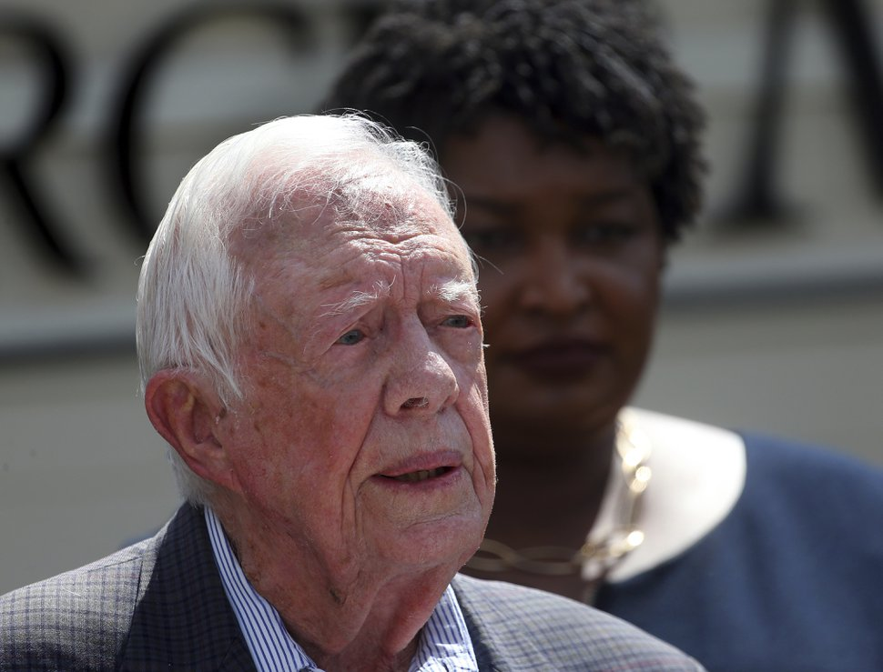 FILE - In this Sept. 18, 2018, file photo, former President Jimmy Carter speaks as Democratic gubernatorial candidate Stacey Abrams listens on during a news conference to announce her rural health care plan in Plains, Ga. Carter is wading into the final days of a Georgia governor's race that's rife with charges and countercharges of attempted voter fraud and attempted voter suppression. In a letter Carter asked Republican nominee Brian Kemp to resign from his post as Georgia secretary of state. Kemp is locked in a tight race with Democrat Stacey Abrams, whom Carter has endorsed. (AP Photo/John Bazemore, File)