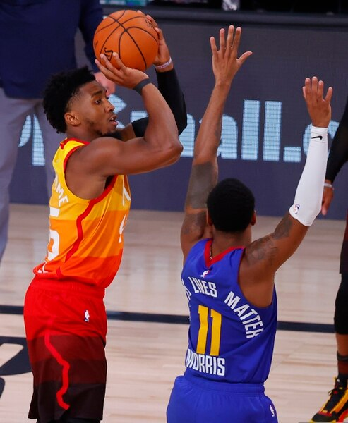 Utah Jazz's Donovan Mitchell shoots a 3-pointer against Denver Nuggets' Monte Morris during the third quarter of Game 4 of an NBA basketball first-round playoff series, Sunday, Aug. 23, 2020, in Lake Buena Vista, Fla. (Kevin C. Cox/Pool Photo via AP)