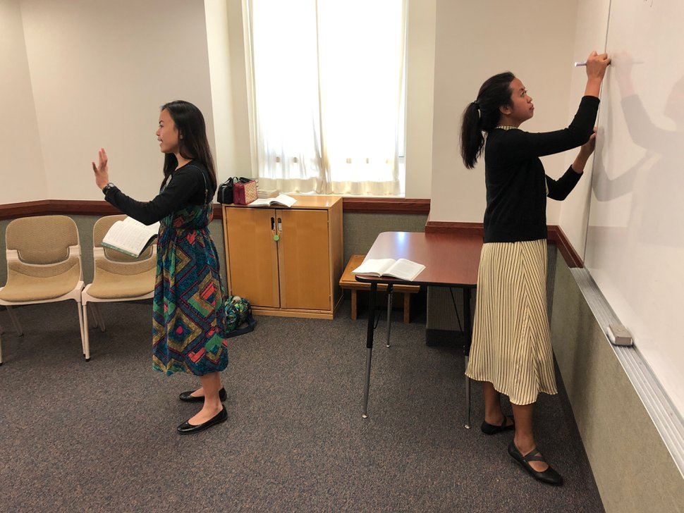 (Mike Stack | for The Salt Lake Tribune) Filipino LDS Missionary Shairyl Arago leads music as her companion Michelle Joy Rodriquez writes on whiteboard in an Everyday branch in central Hong Kong.