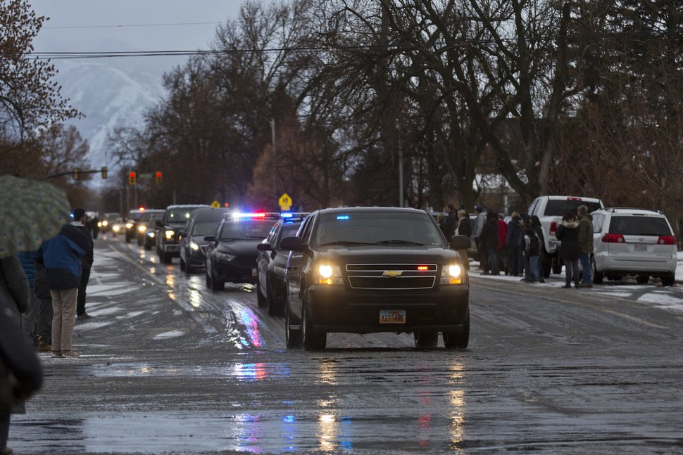A procession of law enforcement vehicles escorting the hearse carrying Provo Police Officer Joseph Shinners makes its way to Wheeler Mortuary in Springville, Utah, Sunday, Jan. 6, 2019. Shinners, who was shot and killed while trying to apprehend a fugitive, was a three-year veteran of the force who managed to shoot back and strike the suspect at least once after he was hit by gunfire. (Evan Cobb/The Daily Herald via AP)