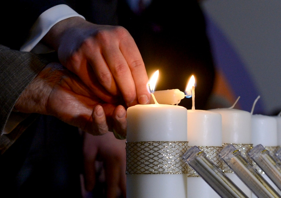 Leah Hogsten | The Salt Lake Tribune Holocaust survivor Abe Katz is aided by Rabbi Avremi Zippel as 11 candles representing those killed during Saturday's shooting at the Tree of Life Synagogue in Pittsburgh are remembered during an interfaith service at Chabad Lubavitch of Utah, Monday, Oct. 29, 2018. Hundreds attended the vigil and prayer service to pray for peace, harmony and love to once again reign supreme upon this Earth.