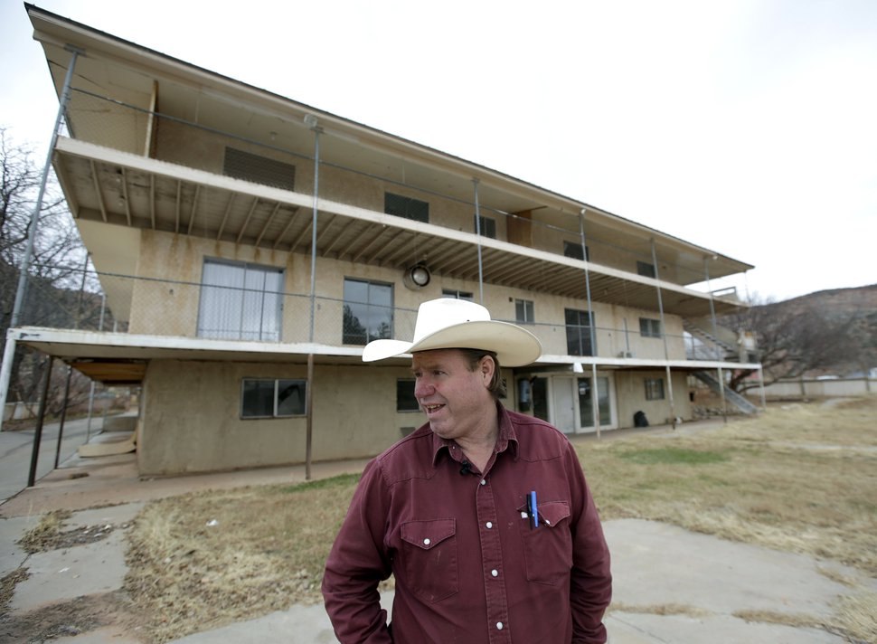 FILE - In this Dec. 16, 2014, file photo, Isaac Wyler, a former member of The Fundamentalist Church of Jesus Christ of Latter-Day Saints, (FLDS) who now works with Utah state officials to handle evictions, stands in front of an evicted polygamous property, in Hildale, Utah. A state-run church trust that controls homes in the polygamous community on the Utah-Arizona has seized 150 homes over the last two years from sect members who refused to pay $100-a-month occupancy fees, with nearly 80 of those homes being sold to former sect members who want to live in the remote village. (AP Photo/Rick Bowmer, File)
