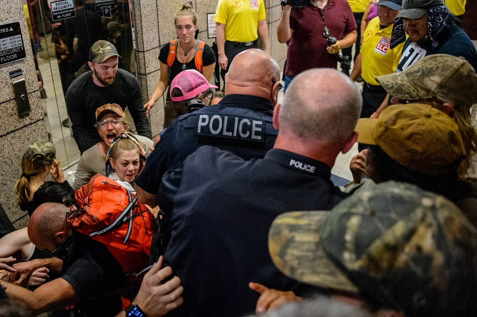 (Trent Nelson | The Salt Lake Tribune) Police wade in to remove protesters occupying the Chamber of Commerce Building Salt Lake City on Tuesday, July 9, 2019. Dozens of people showed up to protest the planned Inland Port. The protest began at City Hall and moved to the Chamber of Commerce.