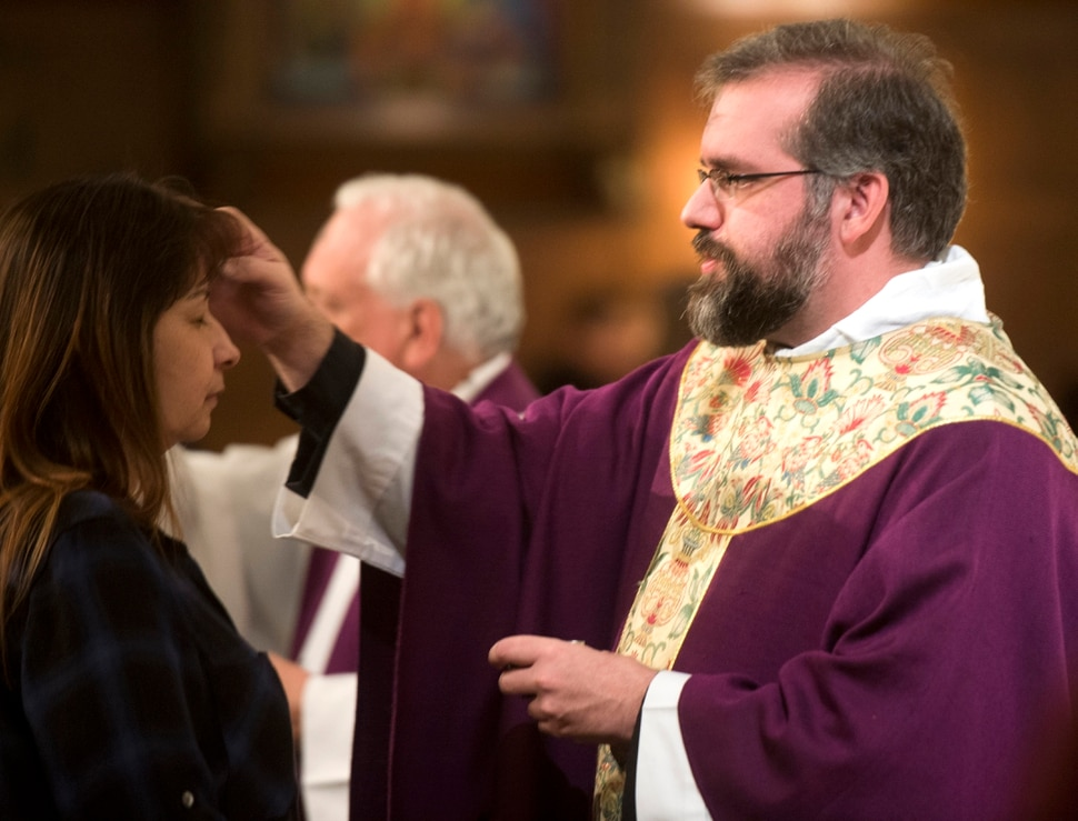 (Rick Egan | The Salt Lake Tribune) The Reverend Christopher P. Gray, dispenses ashes, on the forehead of Brenda Gonzales, during the Ash Wednesday Mass, at the Cathedral of The Madeleine, Wednesday, Feb. 14, 2018.