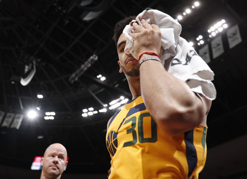 Utah Jazz guard Naz Mitrou-Long holds a towel to his forehead as he bleeds while heading to the locker room after injuring his head in a fall against the Denver Nuggets in the second half of an NBA basketball game Tuesday, Dec. 26, 2017, in Denver. The Nuggets won 107-83. (AP Photo/David Zalubowski)