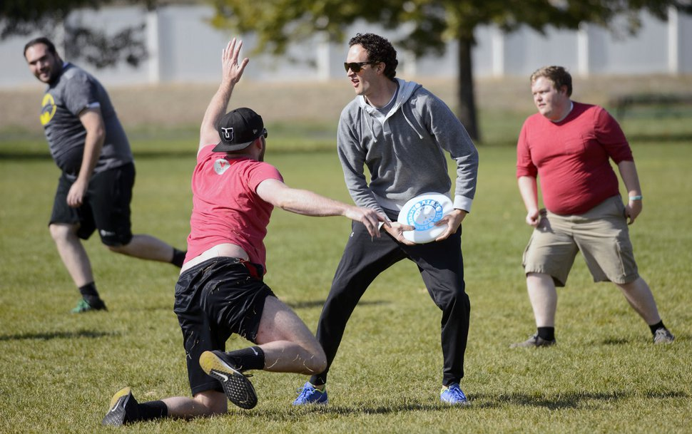 (Steve Griffin | The Salt Lake Tribune) Jared Olsen,of Xima Software, looks to pass as fellow employees play a game of Ultimate Frisbee during lunchtime on River Front Parkway in South Jordan Friday October 13, 2017.