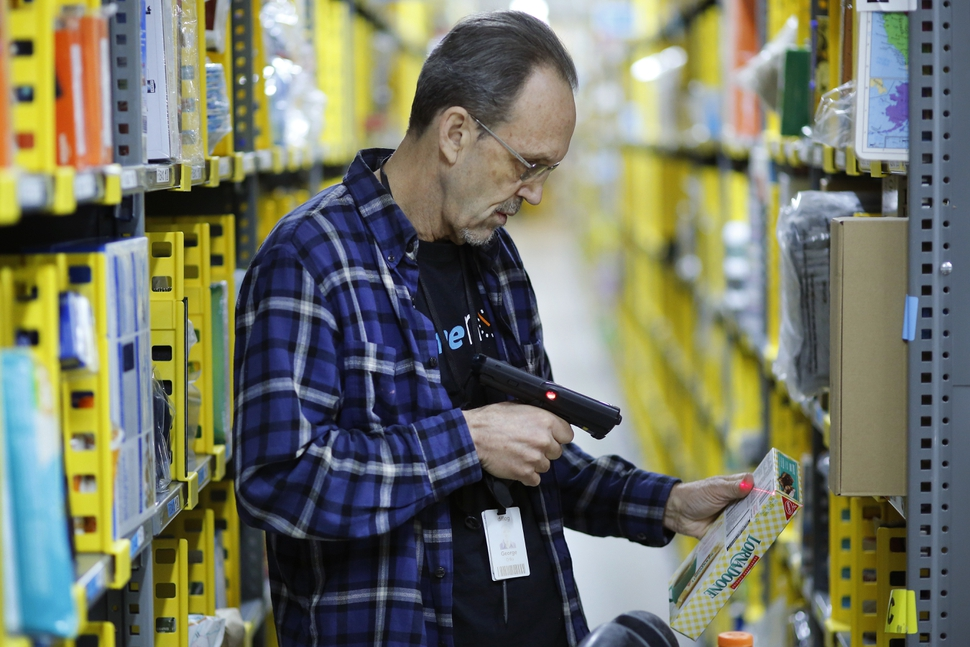 In this Wednesday, Dec. 20, 2017, photo, a clerk picks an item from a shelf and scans it with a hand-held device to fill a customer order at the Amazon Prime warehouse in New York. (AP Photo/Mark Lennihan)