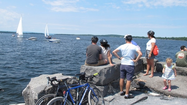 In this July 22, 2017 photo taken in South Hero, Vt., bicyclists watch as boats prepare to pass through a cut in an abandoned railroad causeway from the Vermont mainland to the Lake Champlain islands. The seasonal ferry on the three-mile section of the Island Line Trail bike path carries cyclists across the opening in the causeway so they can reach the islands. (AP Photo/Wilson Ring)