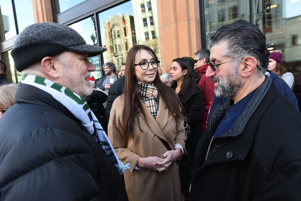 (Francisco Kjolseth | The Salt Lake Tribune) Sculpture artist Daniel Fairbanks, left, joins Shauna Priskos and The Very Reverend Archimandrite George Nikas - Greek Orthodox Church following the unveiling of an eight-foot bronze statue celebrating Shauna's husband, Vasilios Priskos' life and community contributions on Friday, Jan. 3, 2020, along Main Street in Salt Lake City at the entrance of Vasilios Priskos Walkway.