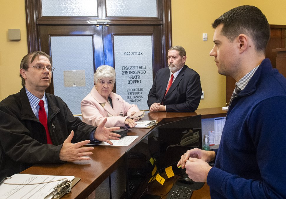 (Rick Egan | Tribune file photo) Former State Rep. Fred Cox, left, Judy Weeks Rohner and Matt Bell file paperwork with Special Assistant Seth Anderson to start signature gathering on an initiative seeking to allow voters to reject the newly-passed tax reform law, at Lt. Governor's Office, Monday, Dec. 16, 2019.
