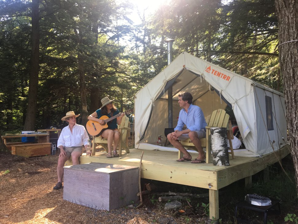 In this Friday, June 29, 2018, photo, Michael D'Agostino, right, sits with Robert and Sally McCracken at their Tentrr campsite in Sand Lake, N.Y. D'Agostino, founder of Tentrr, says it's like Airbnb or Uber for the great outdoors, providing a platform for landowners to earn some cash by sharing secluded and scenic sites for camping. (AP Photo/Mary Esch)
