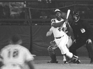 (Harry Harrris | AP file photo)  Atlanta Braves' Hank Aaron eyes the flight of the ball after hitting his 715th career homer in a game against the Los Angeles Dodgers in Atlanta, Ga., in this April 8, 1974 file photo. Dodgers pitcher Al Downing, catcher Joe Ferguson and umpire David Davidson look on. Hank Aaron, who endured racist threats with stoic dignity during his pursuit of Babe Ruth but went on to break the career home run record in the pre-steroids era, died early Friday, Jan. 22, 2021. He was 86. The Atlanta Braves said Aaron died peacefully in his sleep. No cause of death was given.