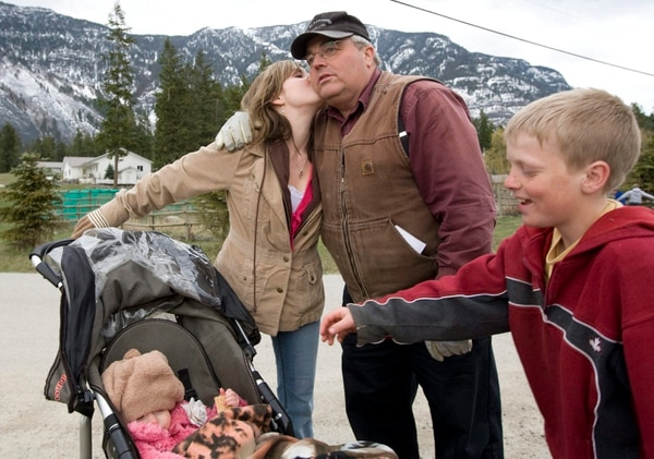 FILE - In this April 21, 2008, file photo, Winston Blackmore the religious leader of the polygamous community of Bountiful located near Creston, British Columbia, Canada receives a kiss from one of his daughters as a son and a grand-child look near Creston. Blackmore has been convicted of practicing polygamy after a decades-long legal fight. Blackmore was found guilty Monday, July 24, 2017, by British Columbia Supreme Court Justice Sheri Ann Donegan. (Jonathan Hayward/The Canadian Press, via AP, File)