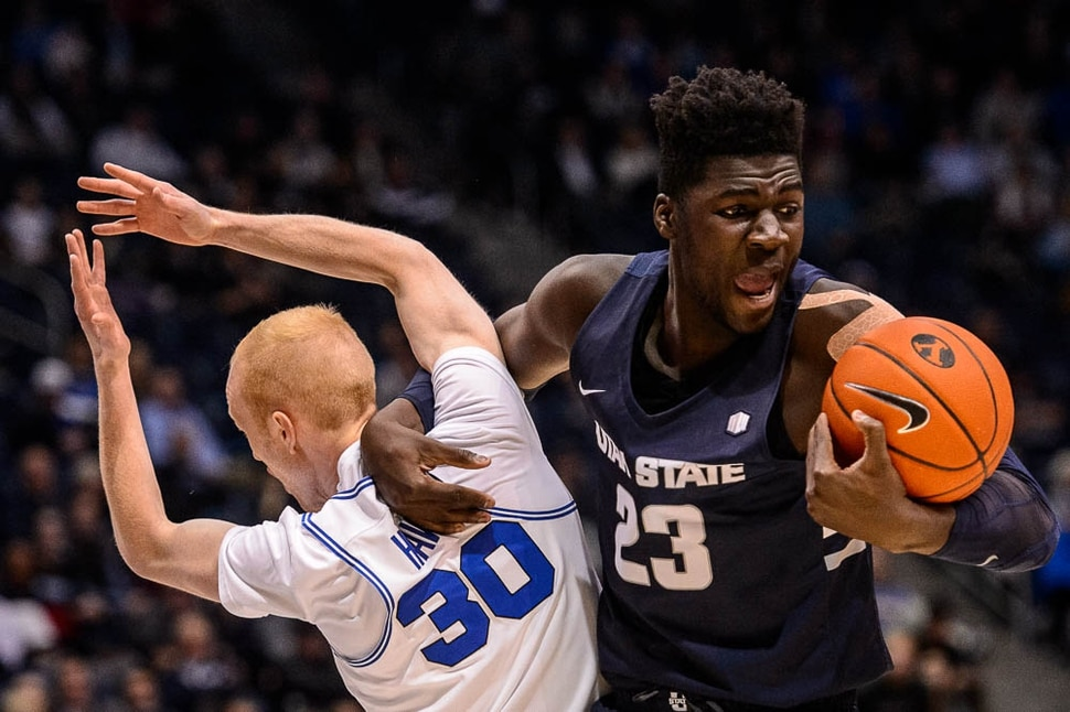 (Trent Nelson | The Salt Lake Tribune) Utah State Aggies center Neemias Queta (23) gets tangled up with Brigham Young Cougars guard TJ Haws (30) as BYU hosts Utah State, NCAA basketball in Provo on Wednesday Dec. 5, 2018.
