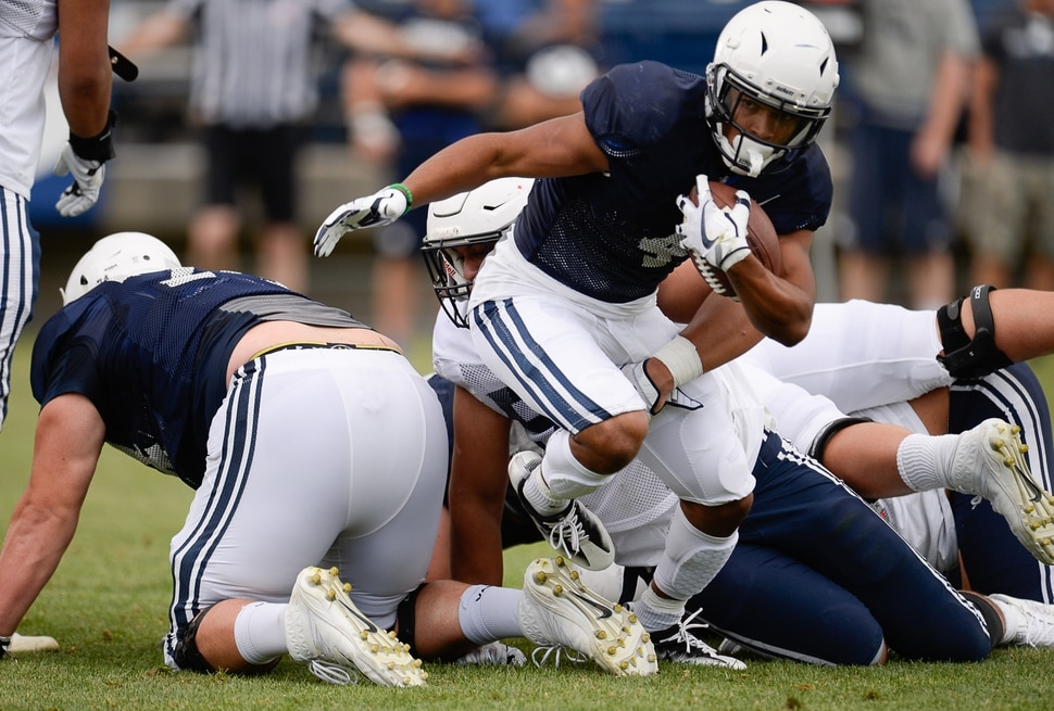 (Francisco Kjolseth | The Salt Lake Tribune) Trey Dye squeezes out from the defense as BYU holds a scrimmage at LaVell Edwards Stadium in Provo on Thursday, Aug. 10, 2017.