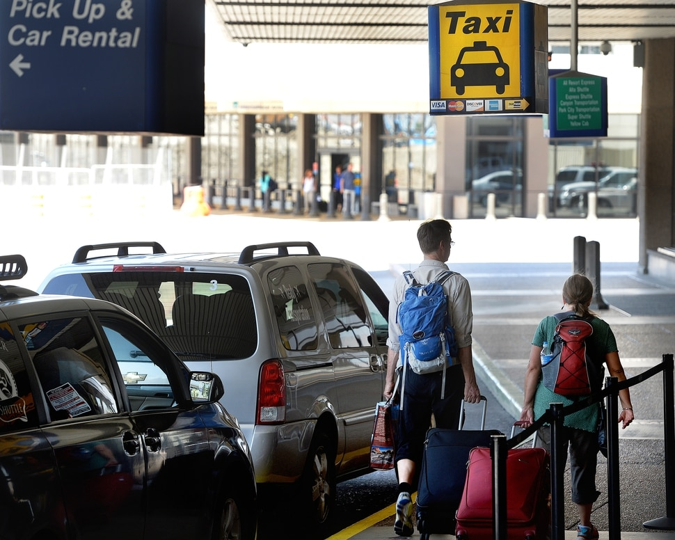 Scott Sommerdorf | The Salt Lake Tribune Travelers walk past the taxi stand at the Salt Lake International Airport, Wednesday, July 20, 2016. There have been some complaints from airport visitors about largely unregulated taxi fares. Cabs no longer need to have meters, can largely charge any fare they want (with some exceptions in SLC itself), and need not tell passengers in advance how much they will charge.