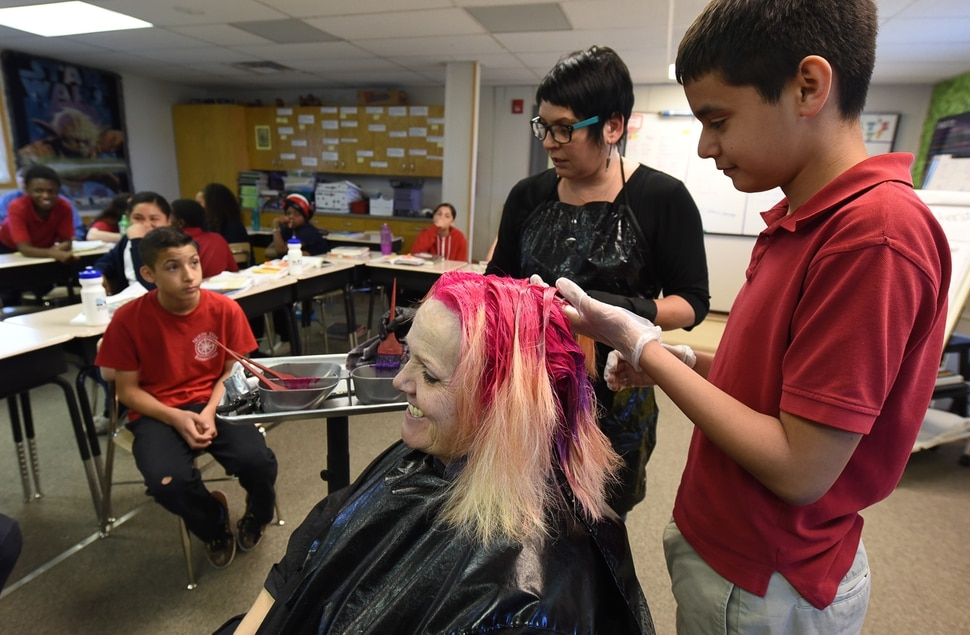 (Francisco Kjolseth | The Salt Lake Tribune) Jonathan Soto, 12, gets a chance to put in some bright pink color into teacher Sharon Moore's hair after the 6th grade teacher at North Star Elementary agreed to the dye on Tuesday, May 8, 2018, after the students SAGE scores went up nearly 17 percent.