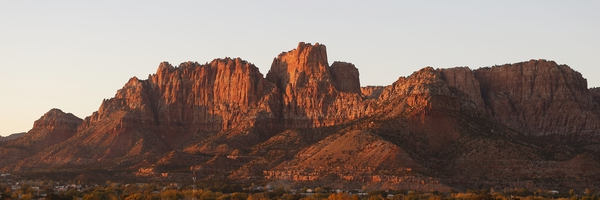 FILE - This Thursday, Oct. 26, 2017, file photo shows the mountains surrounding Hildale, Utah, and its sister city, Colorado City, Ariz., at sunset. The community on the Utah-Arizona border has been home for more than a century to a polygamous sect that is an offshoot of mainstream Mormonism. The new mayor of the mostly polygamous town is finishing off a complete overhaul of municipal staff and boards after mass resignations when she took office in January to become the first woman and first nonmember of the polygamous sect to hold the seat. (AP Photo/Rick Bowmer, File)