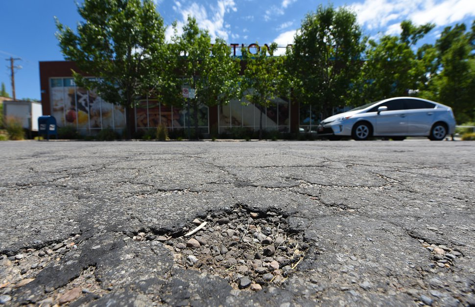 (Francisco Kjolseth | The Salt Lake Tribune) The Salt Lake City Council is on track to authorize a November referendum seeking voter approval for an $87 million bond to fund up to 10 years of catch-up road repairs. The new money for roads would more than double the amount of maintenance the city could do each year — from 75 to 155 lane miles. One road in need of repair is 1700 East near Emigration Market in Salt Lake City, where clear signs of damage can be seen on Monday, July 2, 2018.