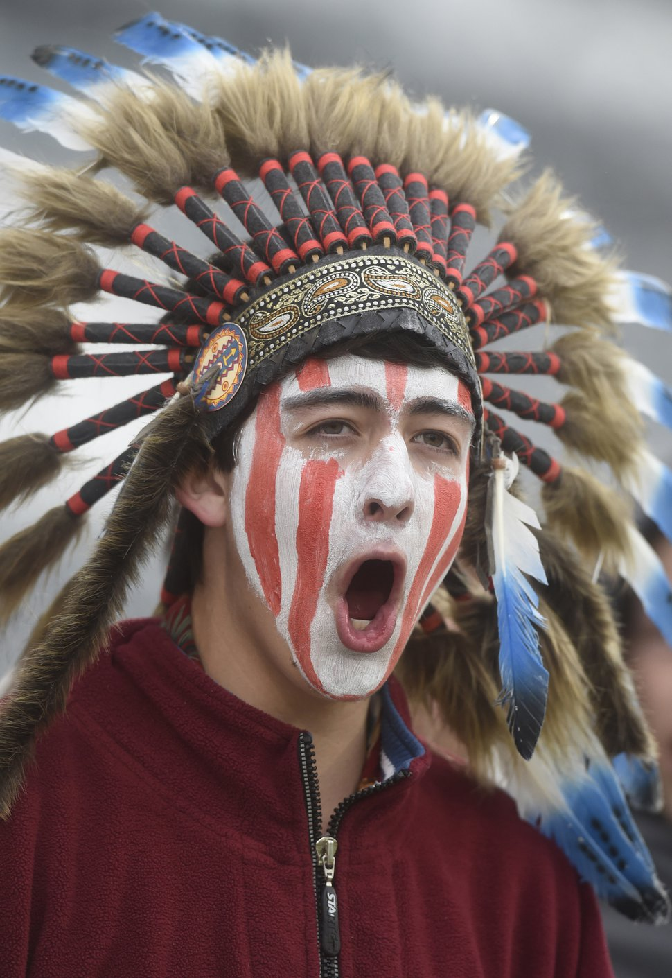 (Mark Reis | The Gazette via AP file photo) In May 2015, a Cheyenne Mountain High School student wears a headdress and face paint as he cheers for his school — which uses