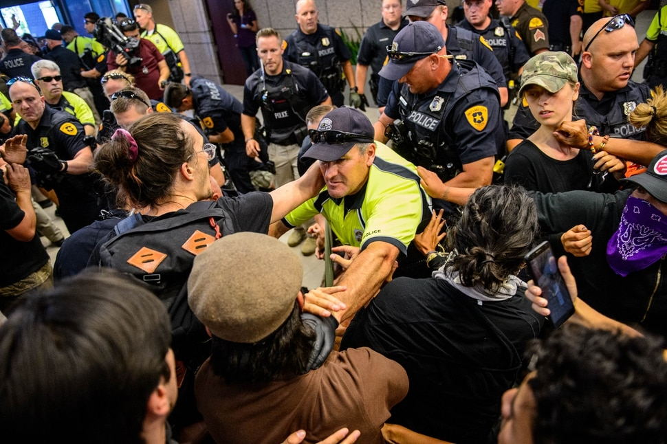 (Trent Nelson | The Salt Lake Tribune) Police remove protesters occupying the Chamber of Commerce Building Salt Lake City on Tuesday, July 9, 2019. Dozens of people showed up to protest the planned Inland Port. The protest began at City Hall and moved to the Chamber of Commerce.