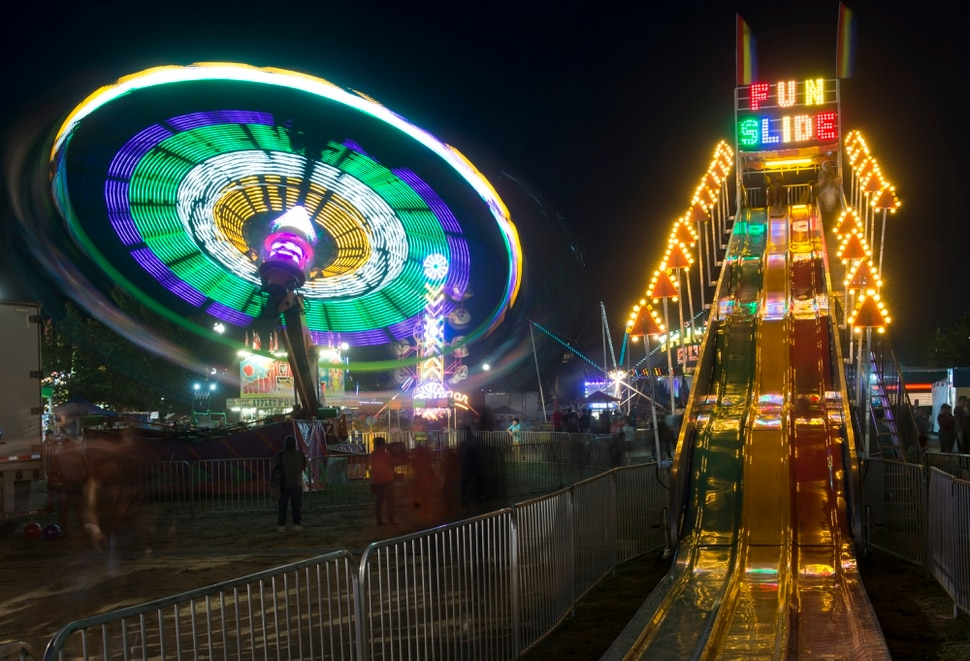 (Rick Egan   The Salt Lake Tribune) The Cliff Hanger and the Fun Slide light up the midway at the Utah State Fair, on a busy Monday evening , Sept. 10, 2018.