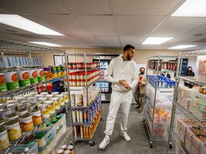 (Trent Nelson     The Salt Lake Tribune) Utah Jazz center Rudy Gobert visits Northwest Middle School to see the new food pantry, in Salt Lake City on Thursday, Oct. 14, 2021. Rudy's Kids Foundation, Smith's Food and the Salt Lake Education Foundation combined efforts to open the food pantry. At rear is James Yapias of the Salt Lake Education Foundation.