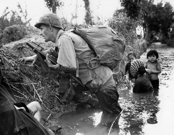 FILE - In this Jan. 1, 1966 file photo, a Paratrooper of the 173rd U.S. Airborne brigade crouches with women and children in a muddy canal as intense Viet Cong sniper fire temporarily pins down his unit during the Vietnamese War near Bao trai in Vietnam. Filmmaker Ken Burns said he hopes his 10-part documentary about the War, which begins Sept. 17, 2017 on PBS, could serve as sort of a vaccine against some problems that took root during the conflict, such as a lack of civil discourse in America. (AP Photo/Horst Faas, File)