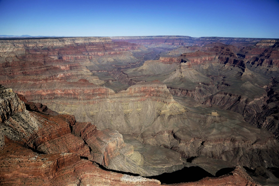 FILE - In this Oct. 5, 2013, file photo, the Grand Canyon National Park is covered in the morning sunlight as seen from a helicopter near Tusayan, Ariz. Arizona officials on Friday, Jan. 19, 2018, guaranteed that the Grand Canyon National Park will remain in full operation if Congress fails to pass a budget and a government shutdown ensues. (AP Photo/Julie Jacobson, File)