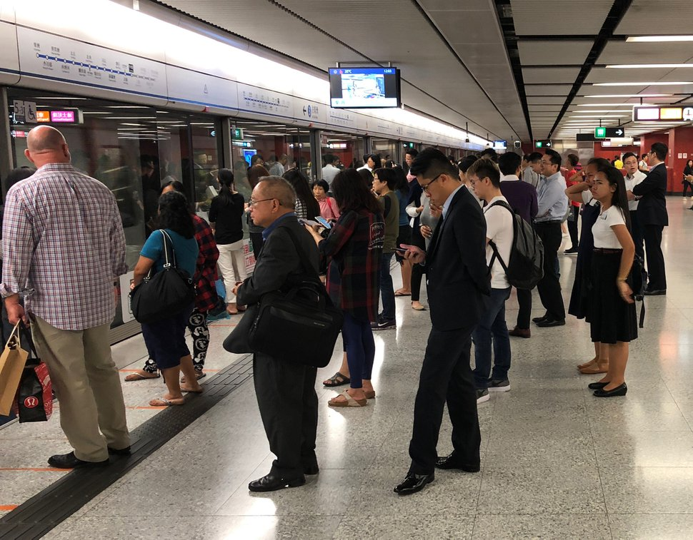 (Mike Stack | for The Salt Lake Tribune) In this file photo, Church of Jesus Christ of Latter-day Saint sister missionaries (far right) wait for train in central Hong Kong.