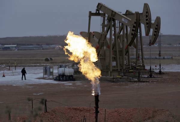 (AP file photo) Workers tend to oil pump jacks behind a natural gas flare near Watford City, N.D. The Trump administration is poised to roll back Obama-era rules on flaring on public lands, including oil and gas operations in Utah. Environmentalists say the reversal will cost taxpayers billions of dollars.