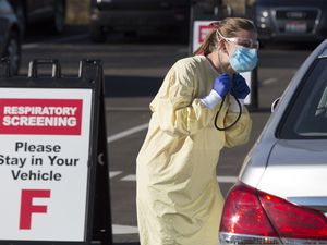 (Otto Kitsinger | AP photo)  Physician assistant Nicole Thomas conducts a COVID-19 examination in the parking lot at Primary Health Medical Group's clinic in Boise, Idaho, Tuesday, Nov. 24, 2020. The urgent-care clinic revamped into a facility for coronavirus patients as infections and deaths surge in Idaho and nationwide. Some 1,000 people have died due to COVID-19, and infections this week surpassed 100,000.