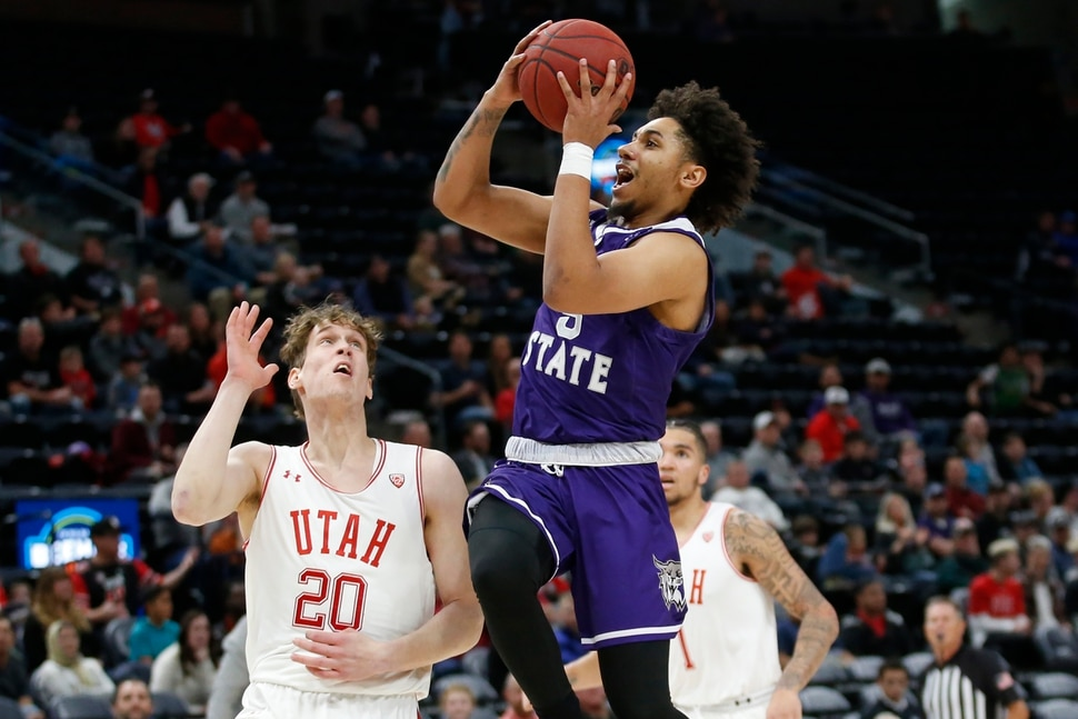 Weber State guard Cody John, right, goes to the basket as Utah forward Mikael Jantunen (20) defends in the first half during an NCAA college basketball game Saturday, Dec. 14, 2019, in Salt Lake City. (AP Photo/Rick Bowmer)